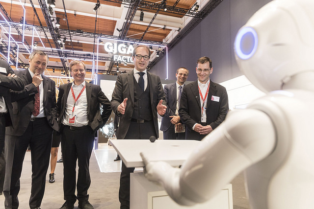 The German minister for transport and digital infrastructure Alexander Dobrindt is playing with the 5G robot at CeBIT 2017.